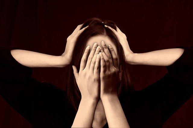 žena, která se drží za hlavu, a další ruce jí svírají hlavu
