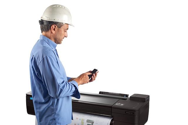 pracovník co drží mobil v ruce a velká průmyslová tiskárny co tiskne