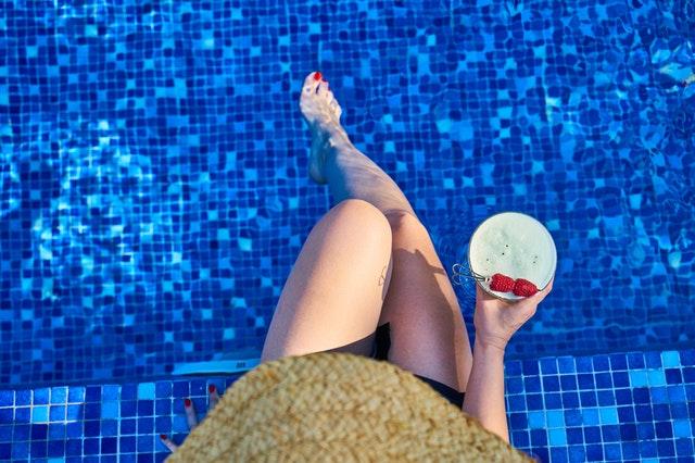 žena se sklenkou u bazénu