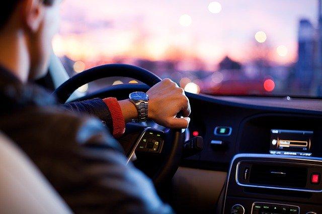 muž sedí v automobilu a řídí